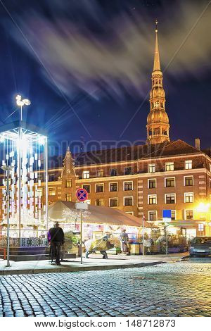People Strolling Around Square With Artistic Christmas Tree In Riga