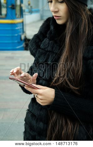 modern technology young girl communicates with friends on social networks together with a few people