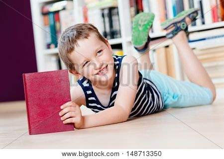 Seven Years Old Boy Reading A Book In Library.