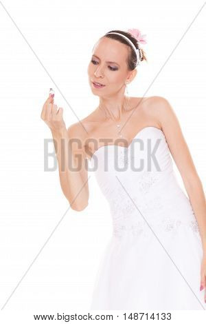 Bride admiring and looking at engagement ring. Woman in white wedding dress isolated on white background.