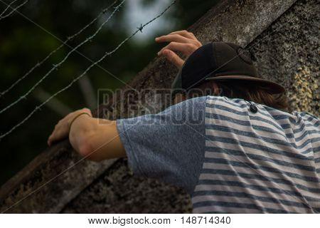 a little boy climbing the wall up