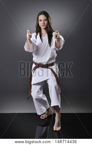 Beautiful Young Brown Belt Female Karate Doing Kata On The Gray Background