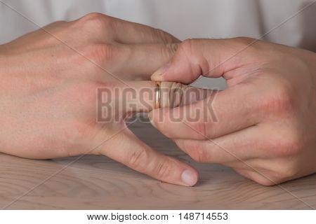 Divorce, separation: hands of man removing wedding or engagement ring