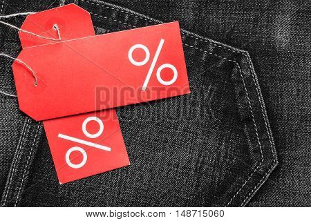 Shopping and sale concept. Closeup two red labels with percent sign and copy space on black jeans pocket denim cotton material background