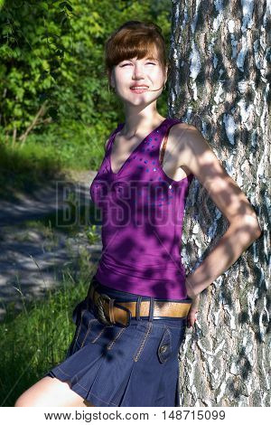 Redhead sexy lady in elegant purple blouse and denim mini skirt posing near birch in summer.Fashion portrait of smiling model outdoors. Beauty chestnut head woman with attractive body in sexy clothes.
