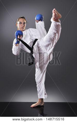 Beautiful young black belt female karate doing kick on the gray background