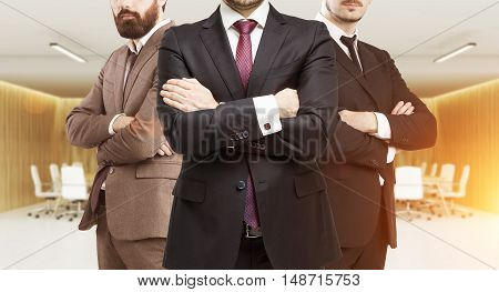Three business partners in suits standing in office meeting room with arms folded. Concept of profitable business. Toned image