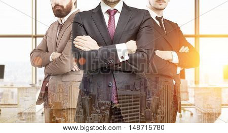 Three business partners in suits standing in office with large windows with arms folded. City panorama at foreground. Concept of successful businesspeople. Toned image. Double exposure