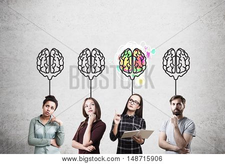 African American lady girl in red dress nerd girl and guy in T-shirt standing near concrete wall with brain images. Concept of brainstorming and genius.