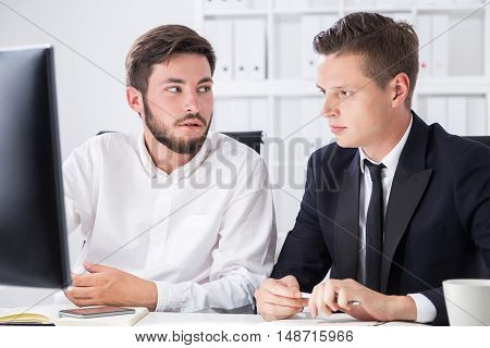 Two partners sit at computer desk in office and talk about current company position on market. Concept of business planning