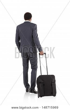 Isolated rear view of African American businessman with suitcase wearing dark gray suit and standing against white background. Concept of business trips.