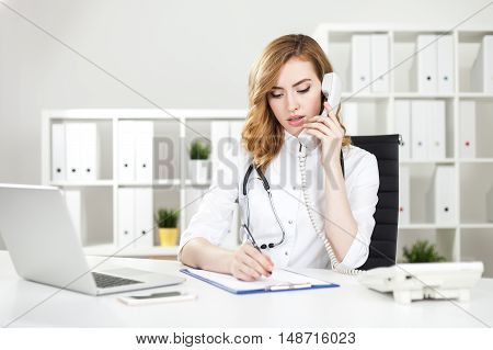 Concentrated woman doctor making phone call and writing down information about her patient. Concept of communication