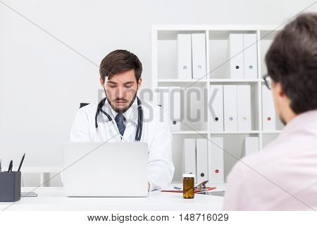 Doctor checking blood test results in hospital's computer system in order to give the right diagnosis to his patient. Concept of medical procedures