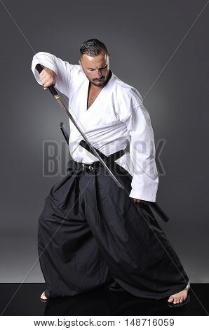 Handsome Young Black Belt Male Karate Posing With Sword On The Gray Background