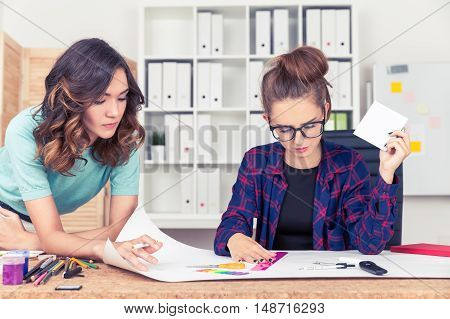 Two Women Drawing A Scheme