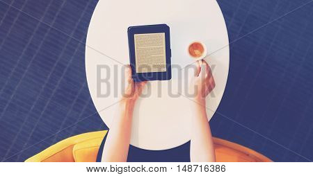 Digital Book Reader And Coffee On Oval Table