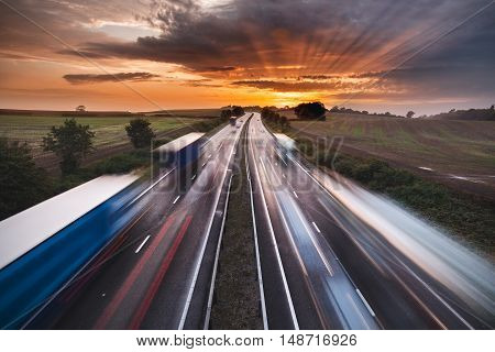 Trails of Lights and Blurred Shapes of Vehicles on Busy Motorway at Sunset