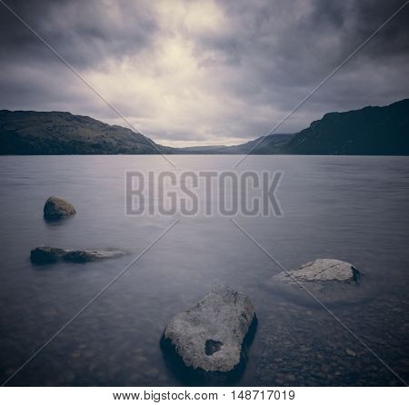 Moody Lake Shore Landscape with Stones Submerged in Water