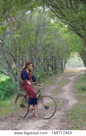 Young asian women sit on an old bike in rice field area.