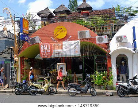 BALI, INDONESIA - SEPTEMBER 17, 2016: Tourists walking past a vegan restaurant, Bali, Indonesia.