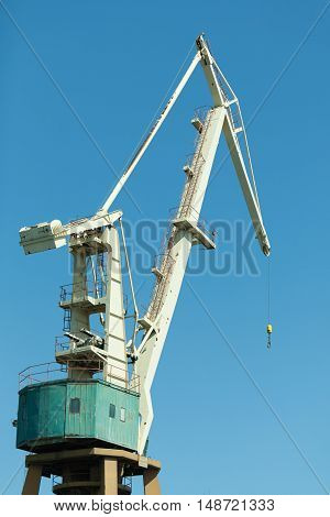 Commerce transport industry cargo machine technology concept. Lonely crane in port. Industrial device in maritime facility.