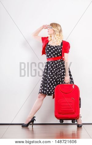 Traveling vacation concept. Elegant young woman in full length wearing polka dot black dress high heels with red suitcase ready for trip journey