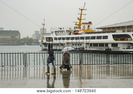 Istanbul Turkey - April 18 2014: Istanbul Kadikoy Steamboat pier. People walking in the rain pier. Strait of Istanbul Kadikoy Pier ferries are the most popular form of public transport in Istanbul for.