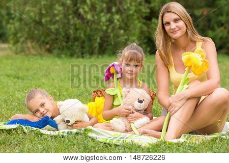 Mother And Daughter Sitting With Soft Toys On A Picnic And Watch The Shot