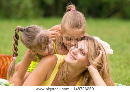 Two Daughter Kissing And Hugging Her Mother Lying On The Grass On A Picnic