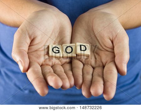 God Spelled in Tiles being held by a young woman