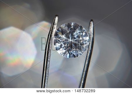 Diamond held by tweezers, close-up