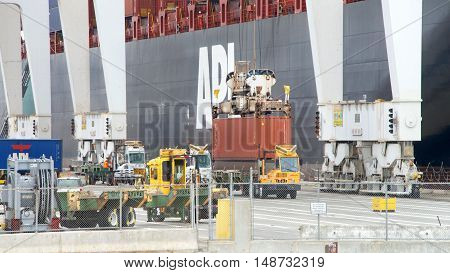 Oakland CA - September 03 2016: Cargo Ship APL SAVANNAH loading at the Port of Oakland. Crane operators can move an average of 30 containers per hour on or off the ships. View from Middle Harbor Park.