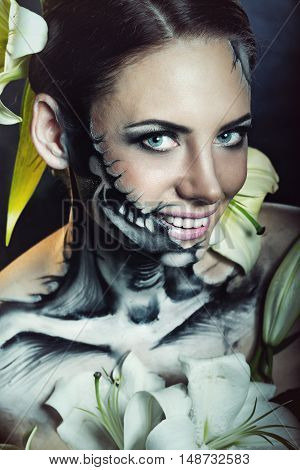 Young attractive girl with creative make-up for Halloween. Mysterious and frightening image of lilies. Witchcraft. Scared.