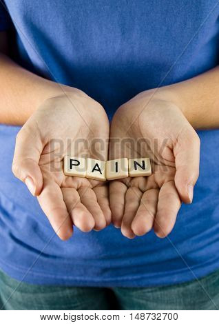 Pain Spelled in Tiles in a young girls hands