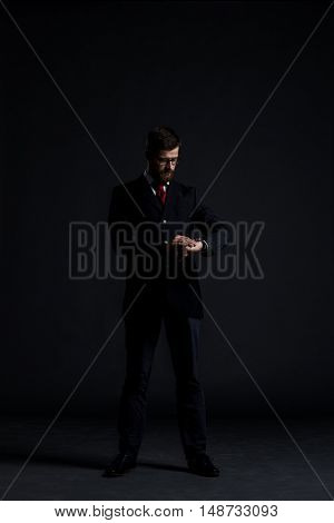 Businessman checking watch over black background. Time, business and office concept.