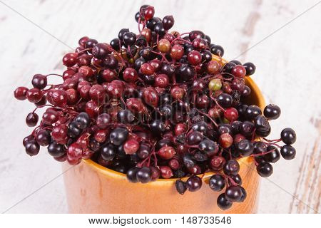 Bunch of fresh elderberry in glass dish on old rustic wooden background healthy food nutrition and alternative medicine
