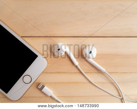 CHIANGRAI THAILAND -SEPTEMBER 15 2016: Front view and close-up image of new Apple iPhone7 mockup Lightning cable and Apple EarPods mockup on wooden background with copy space.