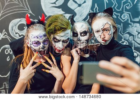 Three girls and a guy going on Halloween, grimace and make selfie