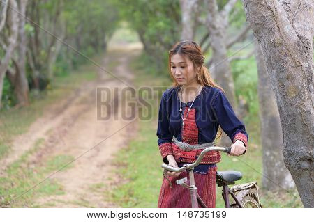 Young asian women haul bike on standing in area field.Thailand