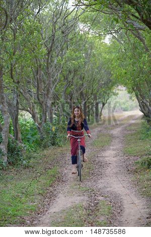 Young asian women riding on an old bike in rice field area.