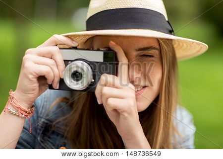 photography and people concept - close up of young woman with camera photographing outdoors
