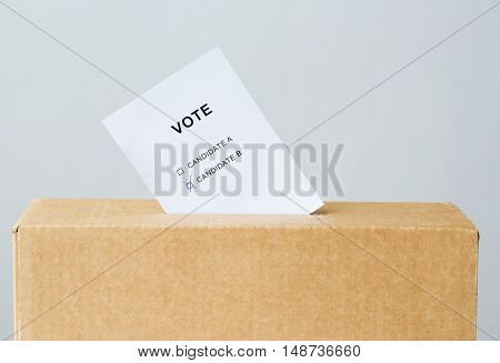 voting and civil rights concept - vote with two candidates inserted into ballot box slot on election
