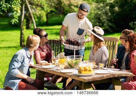 leisure, holidays, eating, people and food concept - happy friends having meat for dinner at summer garden party