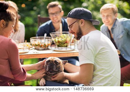 leisure, holidays, eating, people and food concept - happy friends with french bulldog dog having dinner at summer garden party