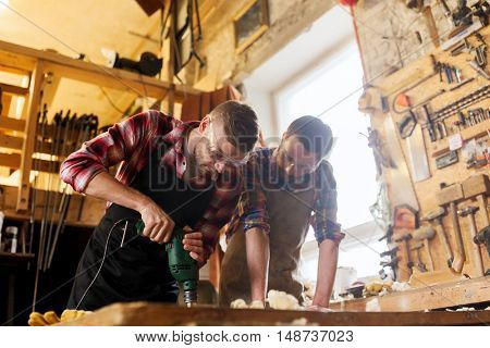 profession, carpentry, woodwork and people concept - two carpenters with electric drill drilling wood plank at workshop