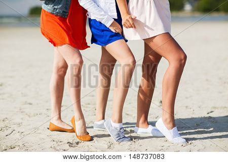 summer vacation, holidays, suntan, epilation and people concept - close up of women legs posing on beach