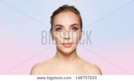 beauty, people and health concept - beautiful young woman face over rose quartz and serenity gradient background