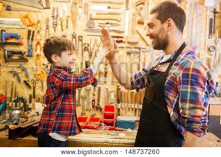 family, carpentry, woodwork, gesture and people concept - happy father and little son making high five at workshop