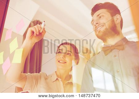 business, startup, planning, management and people concept - happy creative team writing or drawing something on blank office glass board