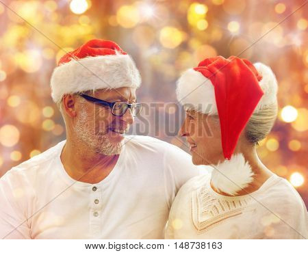 family, holidays, christmas, age and people concept - happy senior couple in santa helper hats over lights background